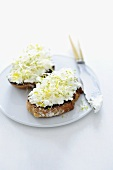 An open sandwich spread with goat's cream cheese and sprouts