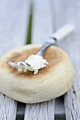 An English muffin and a fork with cream cheese