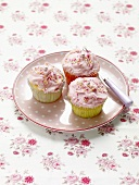 Three pink cupcakes on a polka dot plate