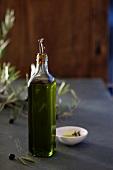 A bottle of olive oil, black olives and a olive sprig