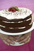 Hands holding a cake stand with a chocolate cream cake