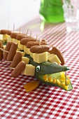A cucumber crocodile with cheese and sausages on sticks for a children's party