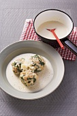 Spinach and bread dumplings in a white cheese sauce