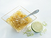 A bowl of lime marmalade with half a lime and zest on the side