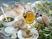 An arrangement of pesto, herbs, olive oil and ciabatta