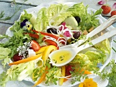 A mixed summer salad with edible flowers and strawberries