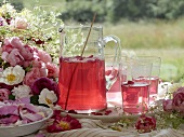A jug of rose petal punch and rose decorations