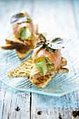 Salmon rolls with avocado on toast triangles