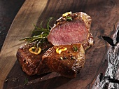 Roast saddle of lamb on a wooden board