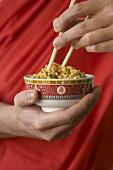 Hand hält Schale mit asiatischem Reisgericht