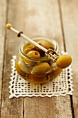 Marinated green olives on an olive fork