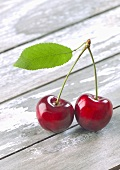 A pair of cherries with a leaf on a wooden table