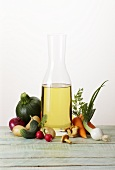 Oil in a carafe with various types of vegetables