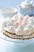 Layered tart with pastel-coloured meringue