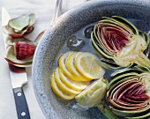 Artichokes and lemon slices in iced water