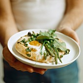 A man holding a pizza topped with egg, peas, asparagus and spinach