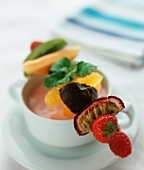 A fruit kebab resting on a soup bowl filled with strawberry quark