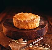 A pork pie on a wooden board