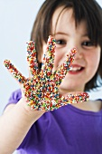 Girl with her hand covered in sprinkles
