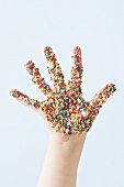 Child's hand covered in sprinkles