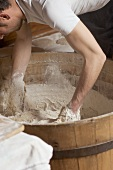Baker kneading dough in a wooden tub