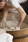 Bäcker knetet Teig im Holzbottich