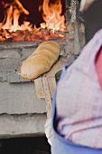 Countrywoman taking freshly baked bread out of stone oven