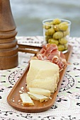 Cheese, raw ham and olives on a wooden platter