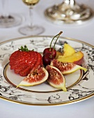 Plate of fruit: fig, strawberry, cherries and peach