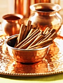 Cinnamon sticks in copper bowl