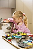 Girl stirring cupcake mixture, decorating ingredients