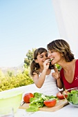 Mother and daughter preparing salad out of doors