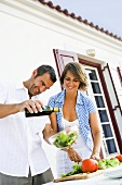 Couple preparing salad out of doors