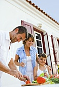 Family with daughter preparing salad out of doors