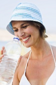 Woman in sun hat drinking mineral water