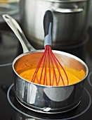 Cream of tomato soup in a pan with a whisk