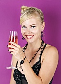 Young woman holding glass of champagne with pomegranate seeds