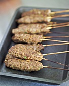 Oven-baked lamb kebabs on a baking tray