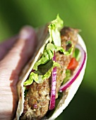 Hand holding pita bread filled with lamb burger and salad