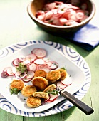 Breaded, fried slices of white sausage with radish salad