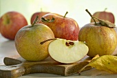 Whole apples and wedge of apple on chopping board