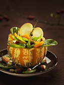 Pumpkin and apple salad in half a pumpkin