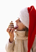 Girl in Father Christmas hat licking biscuit Christmas tree