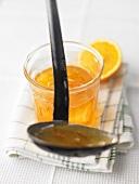 Orange marmalade in jar and on ladle
