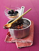 Red grape jelly with pine nuts in pan