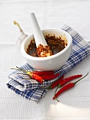 Harissa in mortar, red chillies