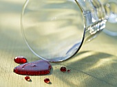 Spilt red wine with upset glass