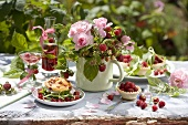 Summery table laid with raspberry dishes out of doors