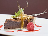 A piece of chocolate torte with a caramel fan and a raspberry