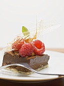 Piece of chocolate tart with a caramel fan and raspberries